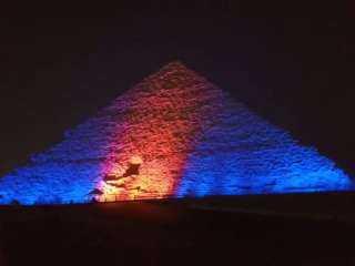 بالصور.. إضاءة الأهرامات باللون الأزرق والبرتقالي بمناسبة اليوم العالمي للكبد